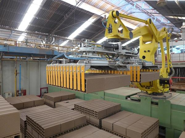 Robot with double head gripper for loading kiln cars.